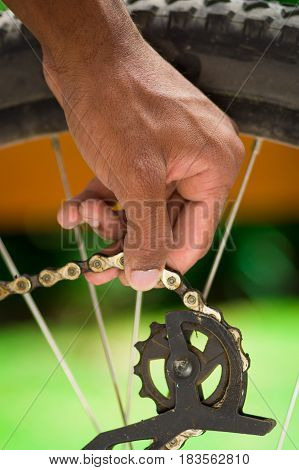 Closeup hand working on mechanical parts next to wheel spokes.