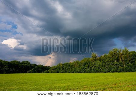 Spring landscape with heavy clouds over the green meadow before the storm