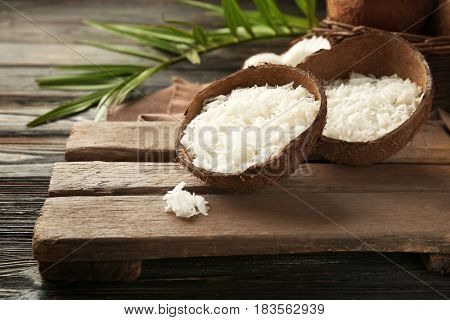 Grated coconut in shell on old wooden board