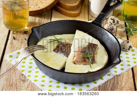 Omelette With Red Fish In A Cast-iron Frying Pan On A Wooden Table. The Concept Of A Healthy Diet An