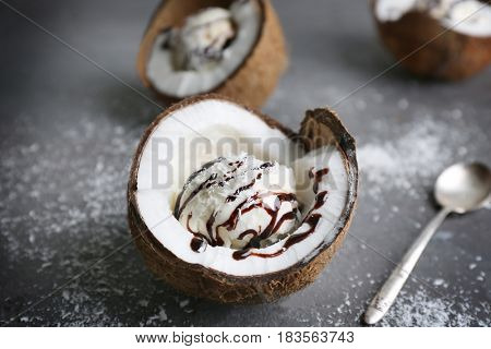 Ice cream with desiccated coconut and chocolate syrup in half of nut on grunge background