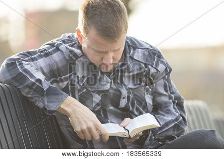 Middle-aged man reading Bible on bench in outdoors