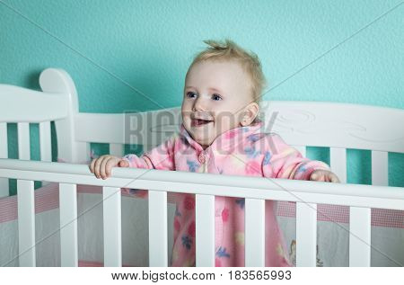A little girl is standing in a baby bed.