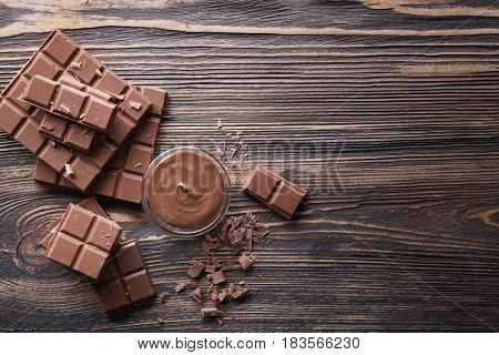 Bowl with melted chocolate and chopped bars on wooden background