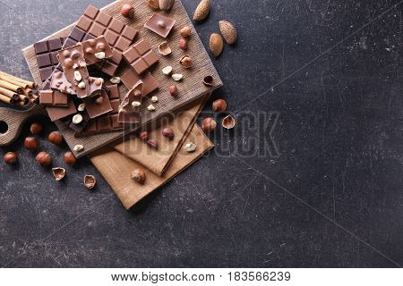 Chopped chocolate bars with nuts on gray background