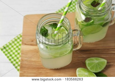 Glass jars of bracing cocktail with lemon slices and mint leaves on wooden board