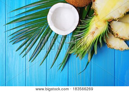 Delicious sliced pineapple and fresh coconut with palm leaf on blue wooden background
