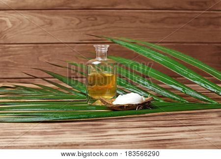 Glass bottle with oil, cream in coconut rind and palm leaf on wooden background