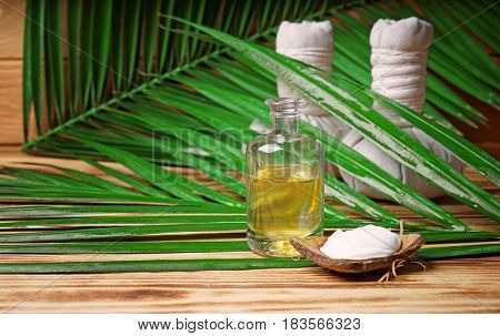 Glass bottle with oil, cream in coconut rind, herbal bags and palm leaf on wooden background