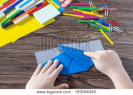 A Child Is Folding An Origami Paper. Handmade. The Project Of Children's Creativity Is A Children's