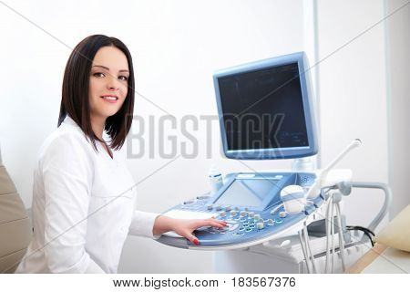 Shot of a cheerful beautiful female doctor smiling to the camera preparing to start ultrasound scanning with sonogram device copyspace technology modern medicine clinic healthcare professionalism job.