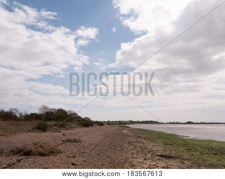 A Landscape Shot Of The Beach And Sea With A Cloudy Blue Sky And Clear Weather