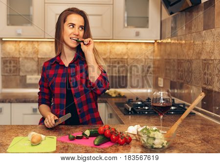 Happy young woman eating slice of cucumber in the kitchen. Woman cutting vegetables for salad.
