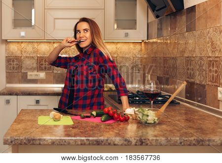 Happy young housewife tasting slice of cucumber from vegetable salad. Woman cooking dinner.