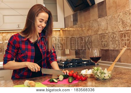 Cooking healthy. Young woman preparing healthy salad and smiling.