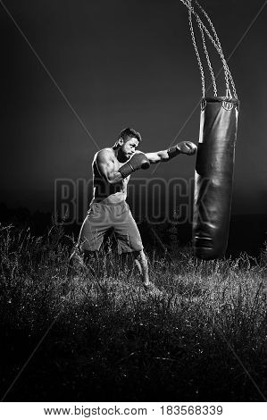 Vertical monochrome shot of a young male boxer with ripped strong muscular body hitting a punching bag working out outdoors at night professional fighter fighting boxing technique skills fitness sport.