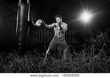 Monochrome shot of a boxer with flaming boxing gloves hitting a punching bag outdoors training at night copyspace sports motivation concentration focus burning fire burn fighting practicing workout.