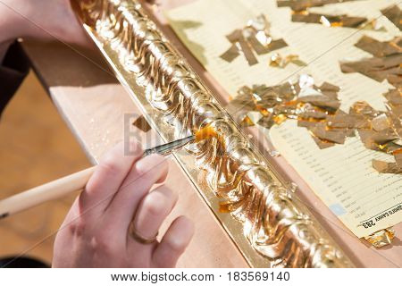 female hand painting with a brush baguette for ceiling and walls in gold color