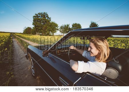 Young female driver driving a big V8 American muscle car on open road. Road trip, journey with classic car.