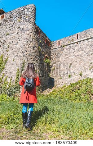 young pretty woman tourist admire of castle wall