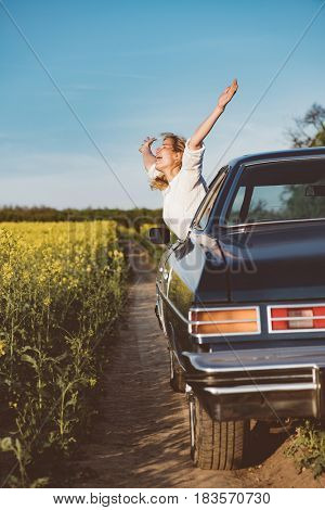 Traveling with fun. Exuberant young woman cheering with excitement as she leans out of the car window with outstretched arms celebrating the start of her summer vacation