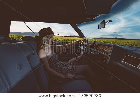 woman in car interior keeps wheel turning around and smiling, female driver against sunset rays
