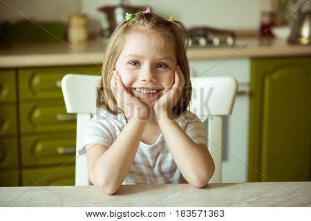 Smiling girl sitting at the table resting his hands on the head