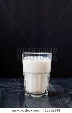 A glass of milk on a dark background. Milk in a glass cup on a dark wooden background. Just milk.