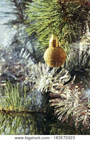 Golden Christmas ball and synthetic spruce branch; selective focus