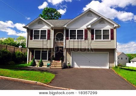 A well maintained typical colonial home on a sunny summer day