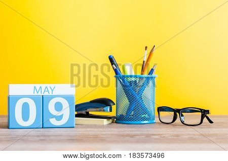 May 9th. Image of may 9 wooden color calendar on blue background. Spring day, empty space for text. Symbols Of the victory in World War II.