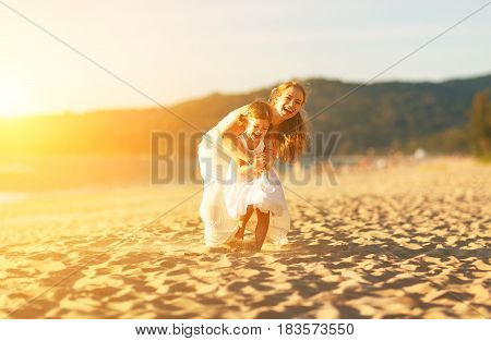 happy family at the beach. motherand child daughter run laugh and play at sunset