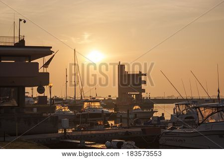 View of several boats moored on the great port of Albarella in Italy illuminated by the warm colors of dawn