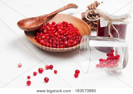 Cranberries in wooden bowl with spoon and cowberry jam in jar on white surface