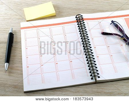 notebook, eyeglasses, pen and yellow blank sticky notes on wooden table floor, diary calendar for planning