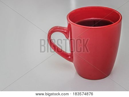 A cup of red color on white. A cup of black tea. Cold tea in a red cup.