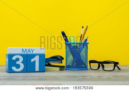 May 31st. Day 31 of month, calendar on business office table, workplace at yellow background. Spring time. World blondes Day.