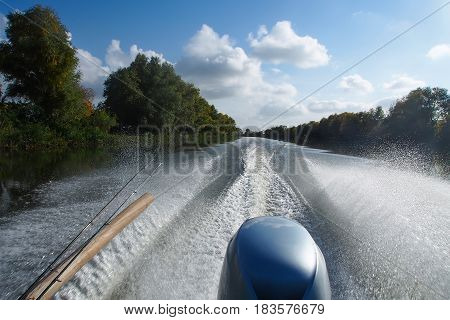 Fishing concept. Fishing boat on river with fishing rods and water splashes.