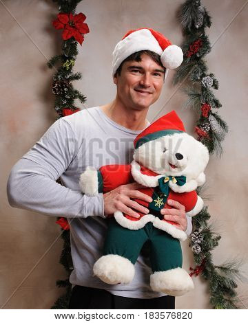 The cute lovable man is holding Christmas teddy.