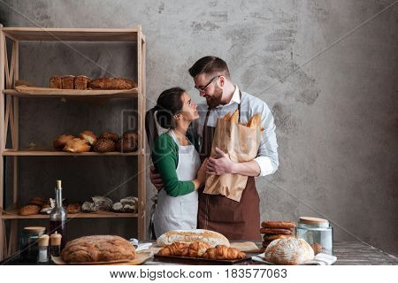 Image of happy loving couple bakers holding bread in hands and looking at each other.