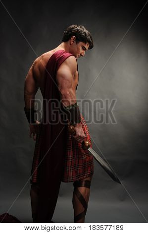 The sexy man is holding a sword ready for battle.