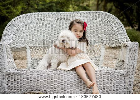 Little hispanic girl hugging her dog sitting on wicker bench