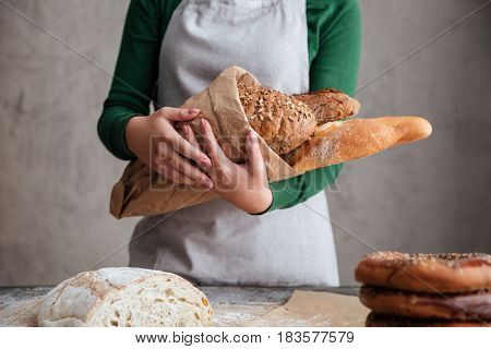Cropped image of  female baker holding bag with bread in bakery