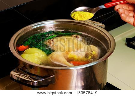 Big chicken is cooked in a saucepan on a gas stove. cooked chicken broth