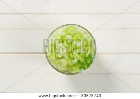 glass of chopped celery stems on white wooden background