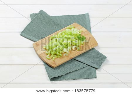 pile of chopped celery stems on wooden cutting board