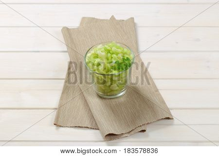 glass of chopped celery stems on beige place mat