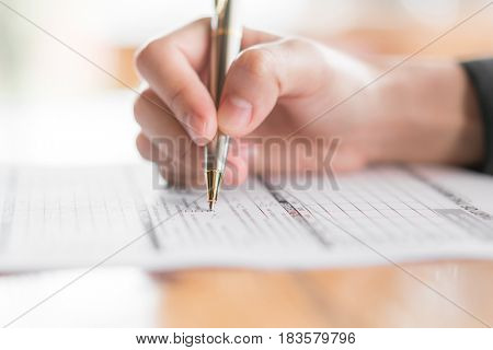 Hand with pen over application form