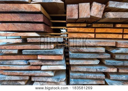 Different size sawn wooden planks stacked in pile and stored for use as building material