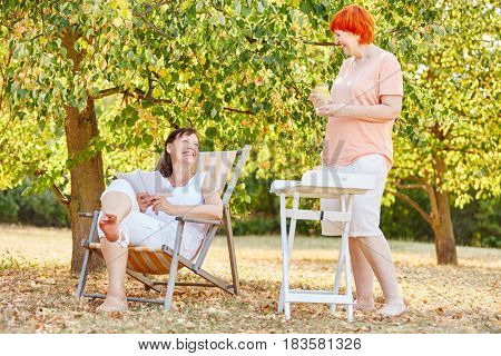 Two women relaxing in the garden in summer on their holiday vacation